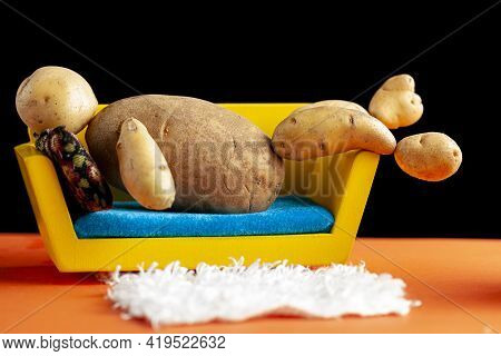A Quirky Metaphorical Concept Image Showing A Potato Man Lying On A Couch In A Living Room Setting.