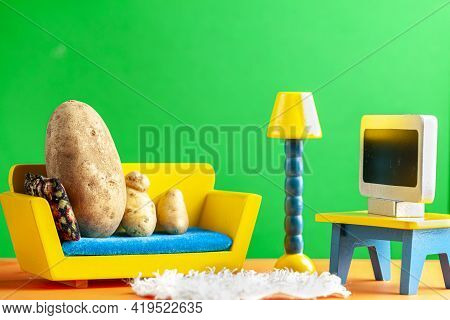 A Quirky Metaphorical Concept Image Showing A Potato Family Lying On A Couch Watching Tv In A Living