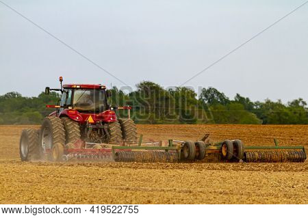 A Red Six Wheel  Tractor With Cabin Is Plowing A Blank Agricultural Field In The Spring. The Attache