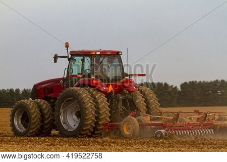 Chestertown, Md, Usa 05-02-2021: Red Six Wheel Case Ih Magnum 305 Model Tractor With Cabin Is Plowin