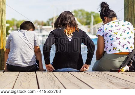 A Hispanic Family With Mother In The Middle And Her Son And Daughter On Both Sides Are Sitting On Th