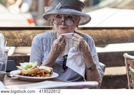 05-02-2021 Annapolis, Md, Usa: An Old Caucasian Lady Wearing A Wide Brim Wedding Hat Is Having A Lun