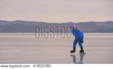 The Child Train On Ice Professional Speed Skating. The Girl Skates In The Winter In Sportswear, Spor