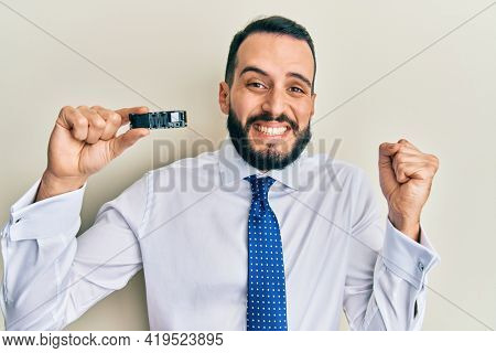 Young man with beard holding ssd memory screaming proud, celebrating victory and success very excited with raised arm