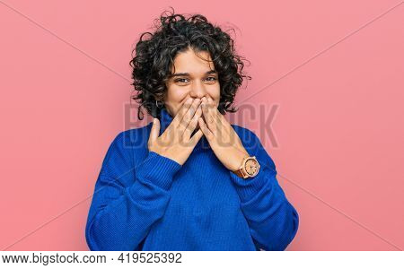 Young hispanic woman with curly hair wearing turtleneck sweater laughing and embarrassed giggle covering mouth with hands, gossip and scandal concept