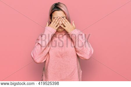 Hispanic woman with pink hair wearing casual winter sweater rubbing eyes for fatigue and headache, sleepy and tired expression. vision problem