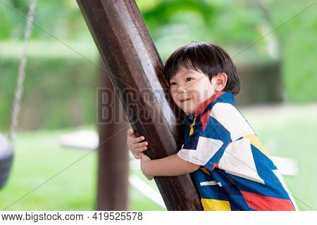Innocent Boy Hugged The Pole And Made A Cute Face. Ragged Child's Face. Children 2-3 Years Old. Happ