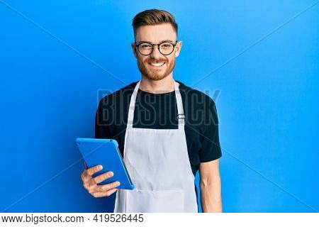 Young redhead man wearing professional apron using touchpad looking positive and happy standing and smiling with a confident smile showing teeth