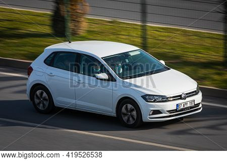 Alanya, Turkey  - April 13  2021:    White Volkswagen Golf   Is Driving Fast On The Street On A Warm