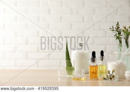Organic Cosmetic Products, Natural Ingredients And Laboratory Glassware On Wooden Table, Space For T