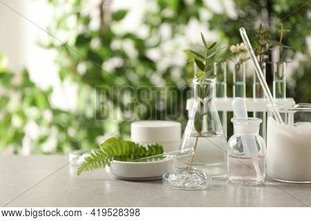 Natural Ingredients For Cosmetic Products And Laboratory Glassware On Grey Table Against Blurred Gre