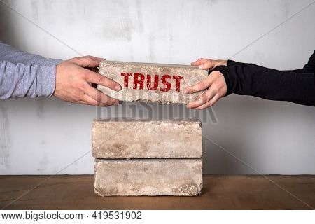 Trust Concept. White Brick Stack On A Wooden Table