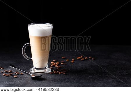 Coffee With Milk, Latte Macchiato In A Glass With A Handle And A Long Spoon On A Black Background, S