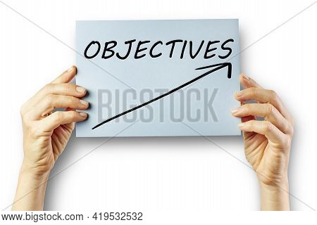 Hands Of A Woman Holding Cardboard With An Arrow And The Word Objectives. Concept Objective