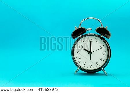 Black Alarm Clock And Space For Text. Retro Alarm Clock On Blue Background
