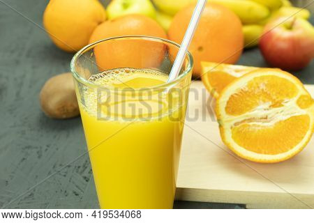 Fresh Orange Juice In A Glass And Fresh Fruits. Cool Orange Juice And Fruits Close Up, Background Wi