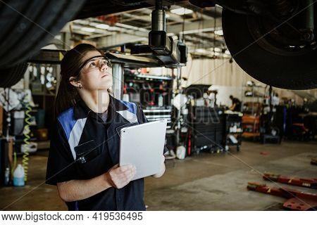 Female mechanic observing a vehicle