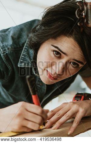 Female carpenter measuring the lumber