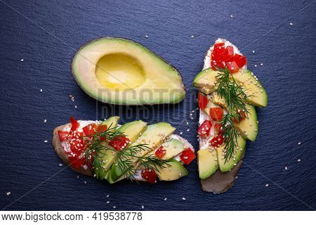 Slices Of Fresh Avocado And Slices Of Ripe Tomato Are Laid Out On A Slice Of Baguette And Sprinkled
