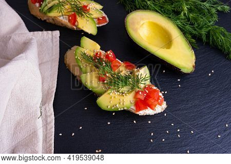 On A Black Background - Half An Avocado, Dill And A Napkin, Canape - Pieces Of A Crispy Baguette Wit
