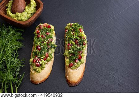 Healthy And Tasty Avocado Canapes, Sprinkled With Ripe Pomegranate Seeds, Sesame Seeds And Fragrant