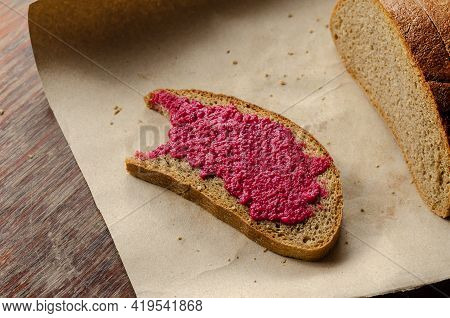 A Bite-sized Slice Of Bread And Fresh Horseradish Sauce With Beets. Uneaten Slice Of Rye Bread With