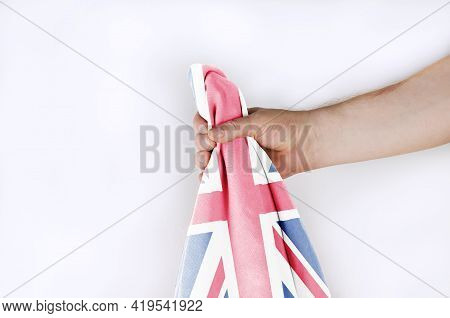 Light National Flag Of Great Britain In Hand Against A White Background. Man Holding The Flag Of The