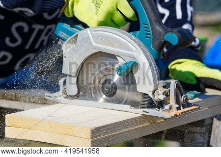 Worker Sawing Wood Board With Electric Circular Saw. Carpenter Working With A Circular Saw Outside I