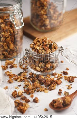 Mason Jar With Granola Breakfast Cereal With Nuts. Wooden Spoon With Scattered Granola In Front And