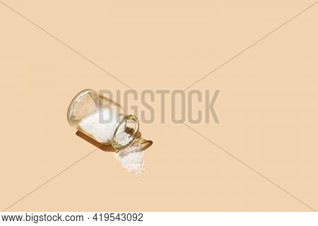 A Glass Jar With Cork Lids Containing Coarse Sea Salt And Sprinkled Salt On Pastel Yellow Seamless S