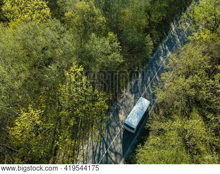 Road with white bus in beautiful summer forest aerial.