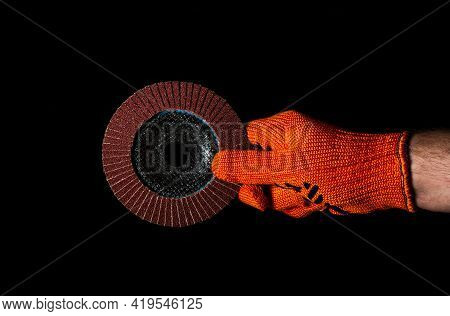 Builder Hand In Glove Keeps Or Gives Abrasive Tools Closeup On Isolated Black Background. The Idea O