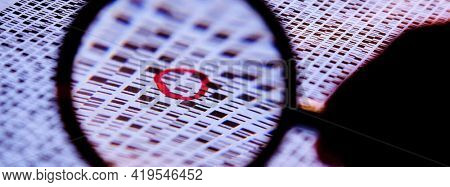Hand with a magnifying glass on the banded DNA sequences