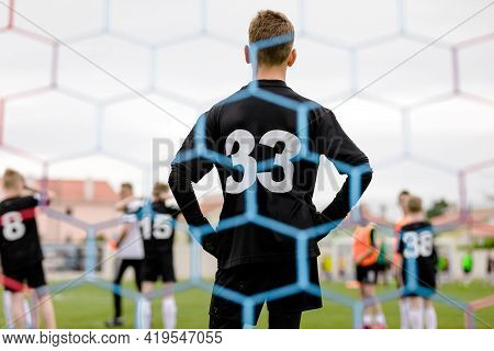 Tall Teenage Goalie Standing In A Goal. Soccer Goal Net In The Blurred Foreground. Young Boy In Foot