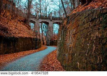 Ancient aqueduct across a ravine in autumn forest