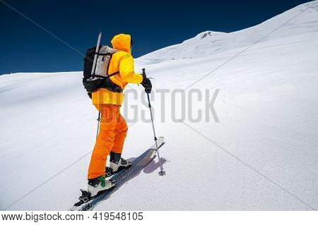 Young Male Freerider Guide In A Yellow Ski Suit With A Backpack On His Shoulders Climbing The Mounta