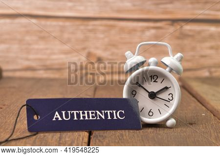 White Clock And Label Tag Written With Authentic On Wooden Board.