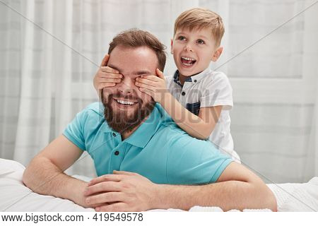 Delighted Boy Smiling And Covering Eyes Of Cheerful Bearded Man While Resting Near Bed At Home