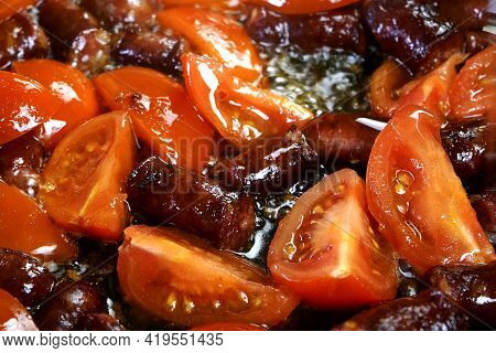Delicious Fatty Hunting Sausages, Cut Into Pieces And Sliced Tomato Are Fried In Frying Pan In Veget