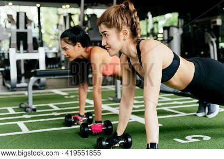 Happy Young Female Athletic People Performing Push-up Exercises With Friend At Fitness Gym. Group Of