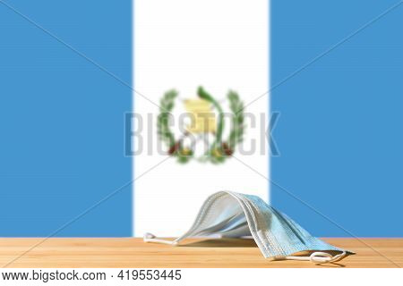 A Medical Mask Lies On The Table Against The Background Of The Flag Of Guatemala. The Concept Of A M