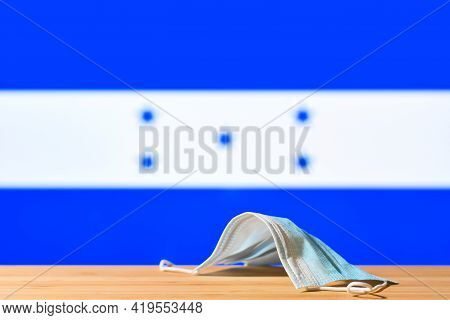 A Medical Mask Lies On The Table Against The Background Of The Flag Of Honduras. The Concept Of A Ma