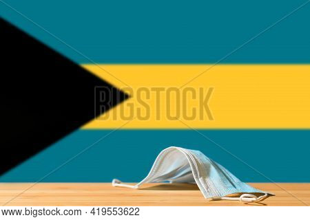 A Medical Mask Lies On The Table Against The Background Of The Flag Of Bahamas. The Concept Of A Man