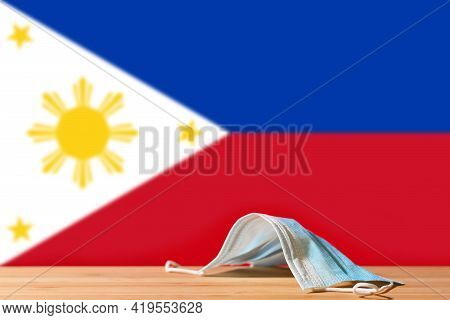A Medical Mask Lies On The Table Against The Background Of The Flag Of Philippines. The Concept Of A