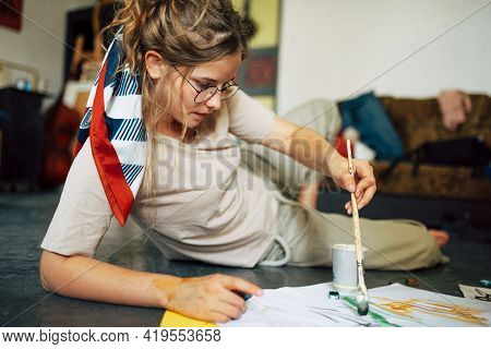 A Female Artist Sitting On The Floor In The Art Studio And Painting On Paper With A Paint Brush. A Y