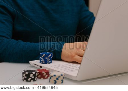 Gamer Man Playing With His Laptop From Home To Casino Games, Poker, Blackjack, Roulette. Concept Of