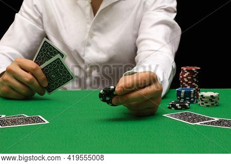 Person In A Night Casino Playing Poker, Gambling Money With Chips. Black Background With Copy Space.