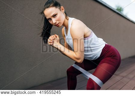 An Athlete Female Working With The Elastic Band Outside On Grey Background. Healthy Fit Woman Exerci