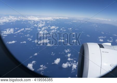 Plane Engine And Blue Sky With Small White Clouds Through Window While Travelling.