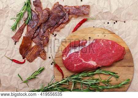 Jerky Meat And Raw Beef On Brown Craft Paper Background. Ingredients For Cooking Meat Snacks. Rosema